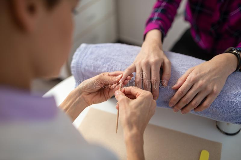 Manicure professionista che pulisce le unghie femminili fotografia stock libera da diritti