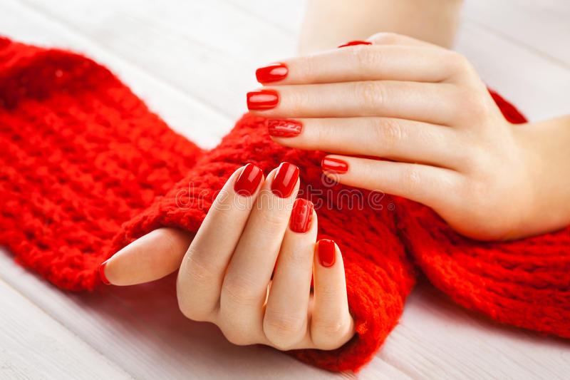 Manicure with a red knitted scarf. Red manicure with a red knitted scarf on the white wooden table royalty free stock photos