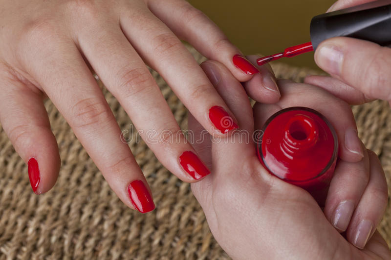 Manicure with a red polish nails. Manicure in a cosmetic center and red nail polish on female hands stock photos