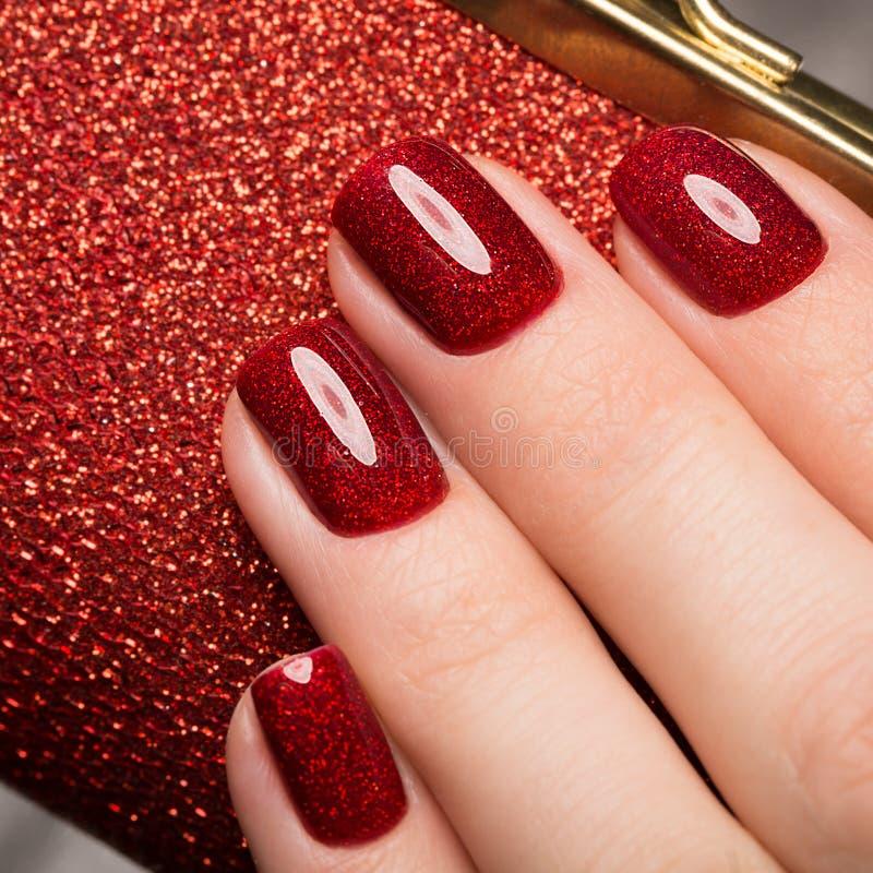 Manicure rosso festivo luminoso sulle mani femminili Progettazione dei chiodi immagine stock libera da diritti