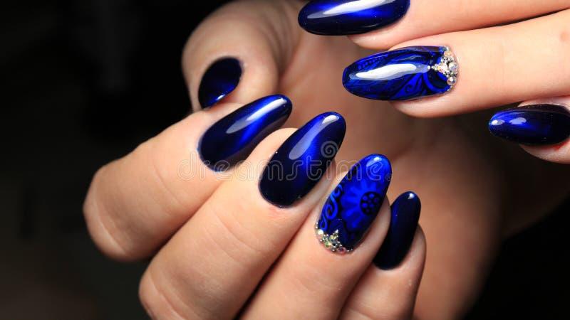 Manicure, s-oeil de ` de chat et poli de gel en verre souillé de bleu avec une photo et des fausses pierres photo libre de droits