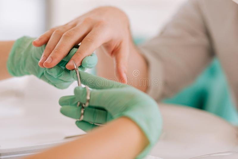 Nail master wearing gloves holding manicure scissors cutting cuticle. Manicure scissors. Nail master wearing gloves holding manicure scissors cutting cuticle for stock photo