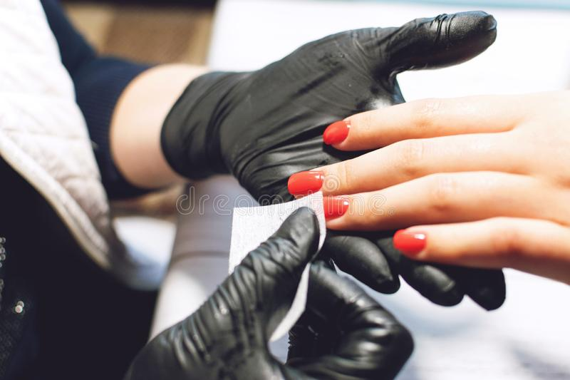 Manicure specialist in black gloves cares about hands nails. Manicurist paints nails with red nail polish.  Manicure beauty salon stock images