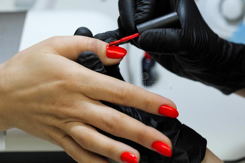 Manicure specialist in black gloves cares about hands nails. Manicurist paints nails with red nail polish stock images