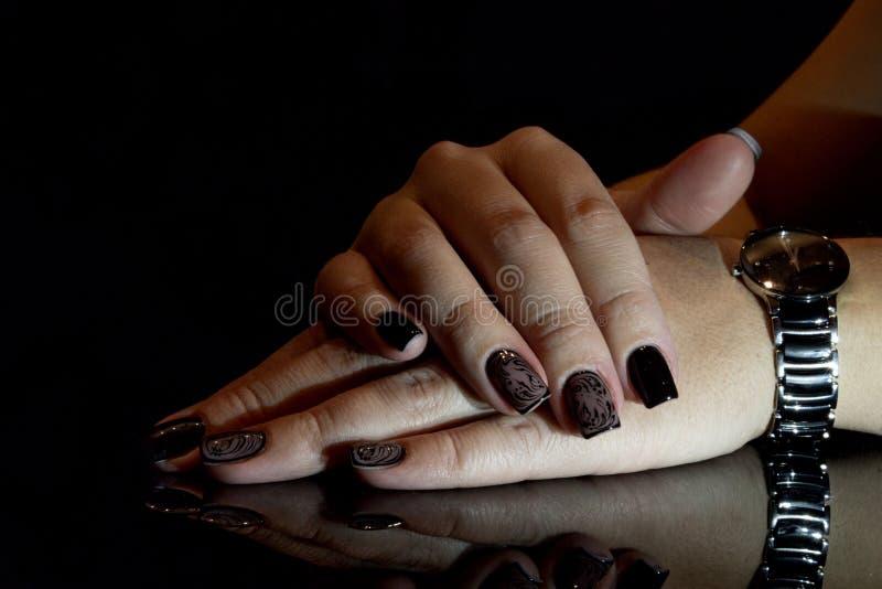 Manicure splendido, smalto nero di colore, foto del primo piano Mani femminili con fondo scuro immagine stock libera da diritti