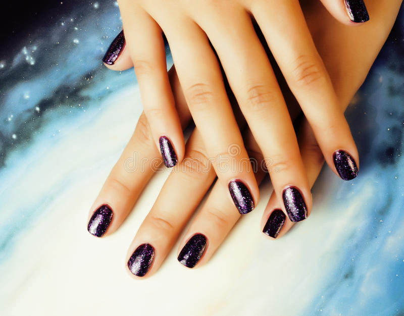 Manicure stylish concept: woman fingers with nails purple glitter on nails like cosmos, universe background. Close up stock image