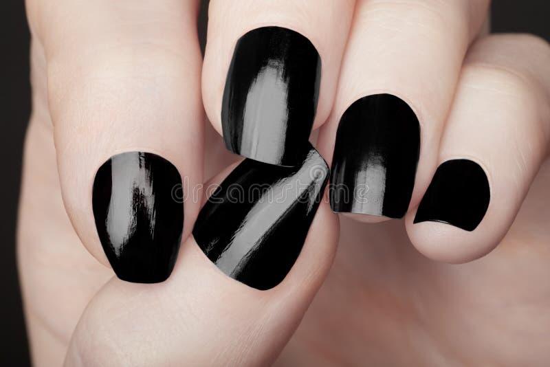 Manicure sulle mani femminili con smalto nero fotografia stock