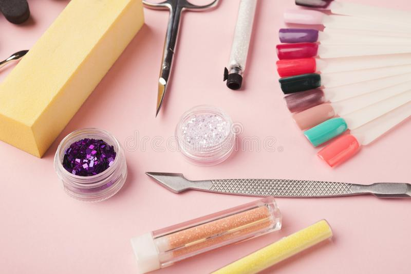 Manicure supplies on pink background. Manicure and pedicure beauty accessories on pink background, copy space. Nail polish samples, scissors, clippers and other stock photography