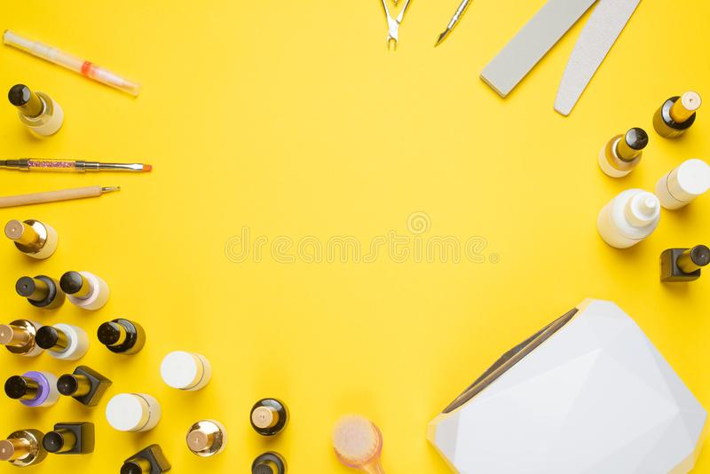 Manicure - tools for creating, gel polishes, everything for nail care, beauty and care concept. Banner for inscriptions salon. Yellow background Flat-lay royalty free stock photography
