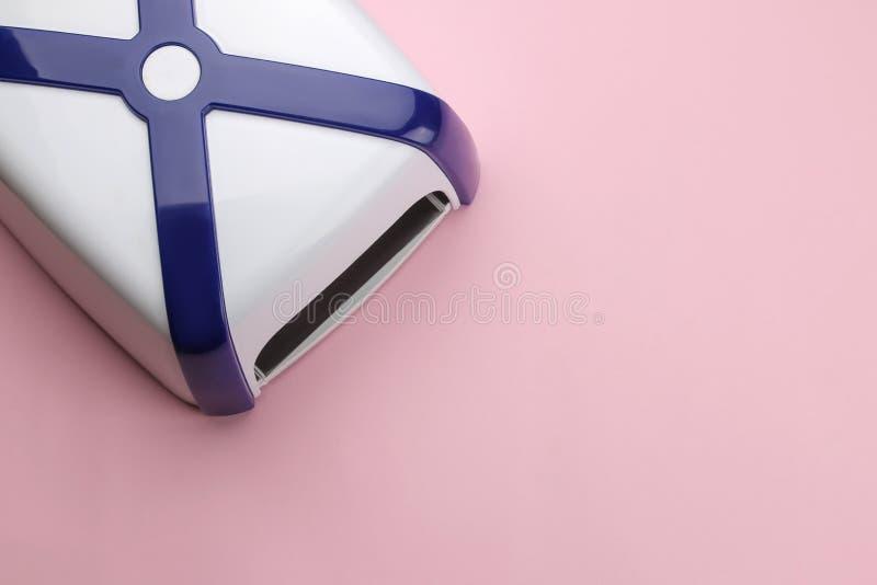 manicure ULTRAFIOLETOWA lampa na delikatnym różowym tle Manicure narzędzia dla gwoździ i akcesoria Odgórny widok obrazy stock