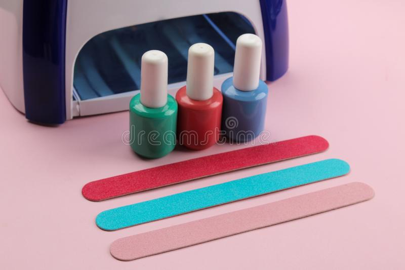 Manicure. UV lamp and nail files and nail polishes on a gentle pink background. Manicure accessories and tools for nails stock photos