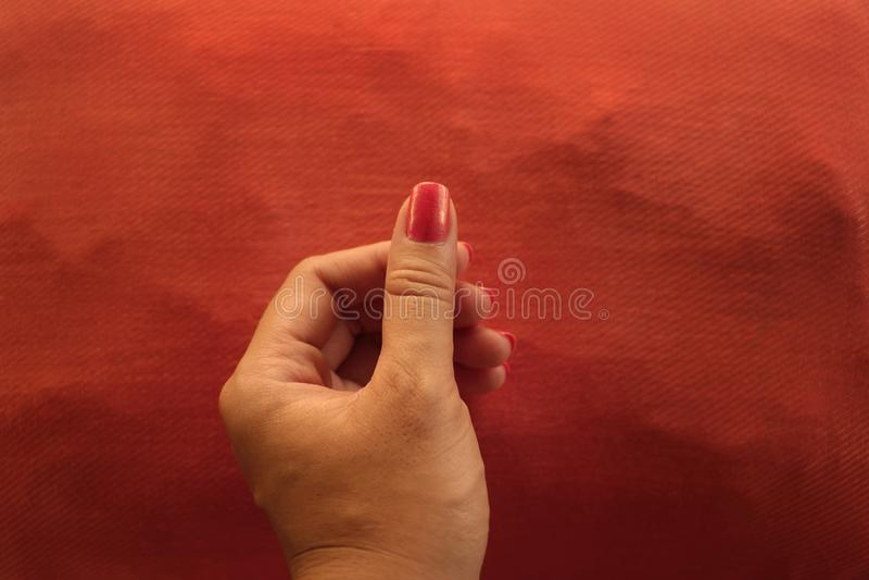 Manicured πορτοκαλιά εκμετάλλευση χεριών καρφιών πολωνική κάτι στο ταίριασμα του μαξιλαριού στοκ εικόνα