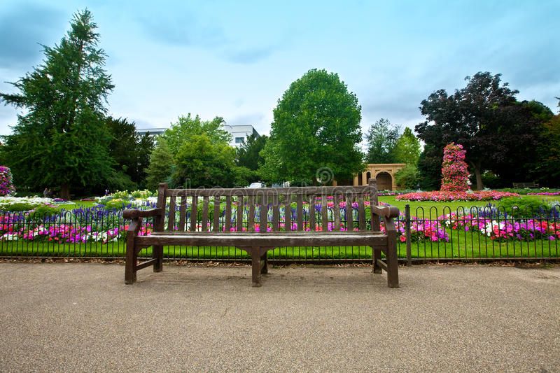 Download Manicured Flower Garden With A Wooden Bench Stock Photo - Image of nature, chair: 24129418