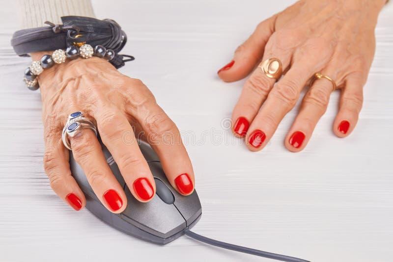 Manicured hand för gammal kvinna genom att använda PCmusen royaltyfria foton