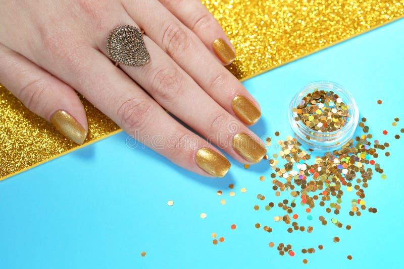 Manicured handen för kvinnan spikar blänker visningen med guld- polermedel och på färgbakgrund arkivfoto