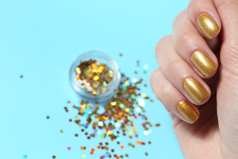 Manicured handen för kvinnan spikar visningen med guld- polermedel över färgbakgrund, closeup royaltyfri foto