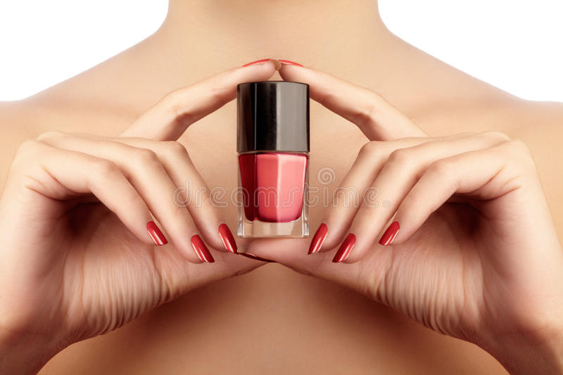 Manicured nails with red nail polish. Manicure with bright nailpolish. Fashion manicure. Shiny gel lacquer in bottle.  royalty free stock photos