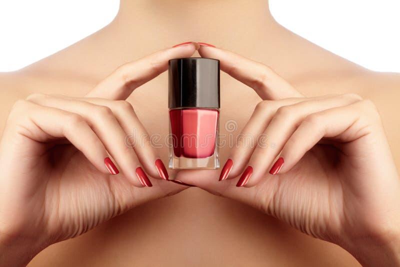 Manicured spikar med rött spikar polermedel Manikyr med ljust nailpolish Modemanikyr Skinande stelna färg i flaska royaltyfria foton