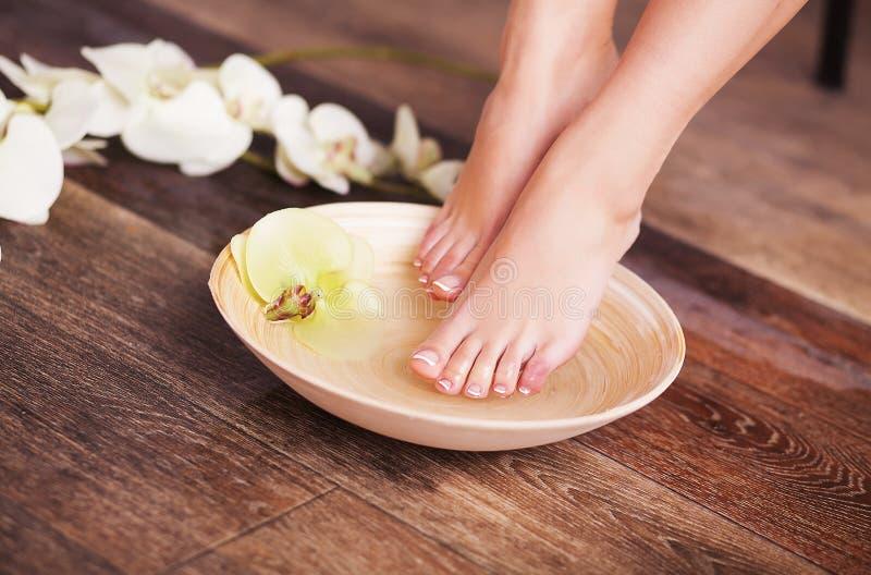 Manicured vrouwelijke voeten in kuuroord houten kom met bloemen en waterclose-up royalty-vrije stock foto