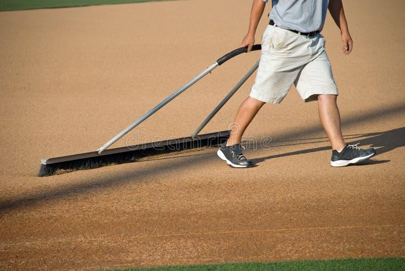 Manicuring el campo de béisbol fotografía de archivo libre de regalías