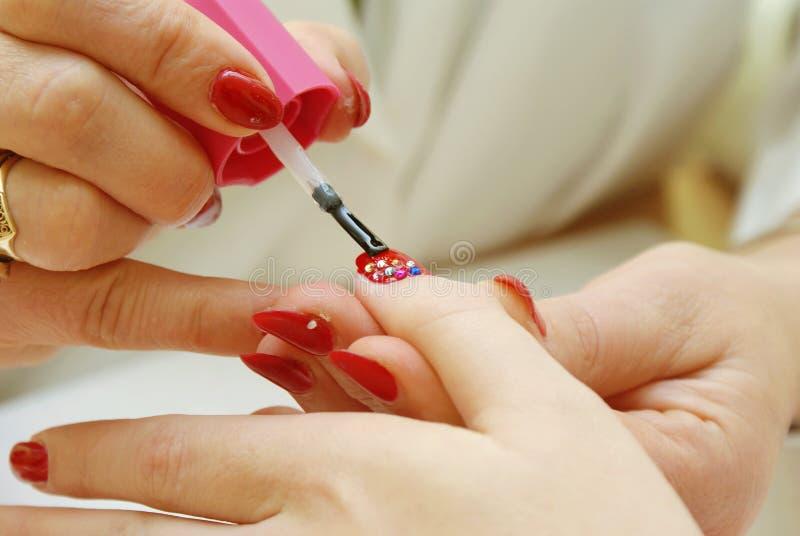 Manicurist che applica chiodo rosso immagine stock