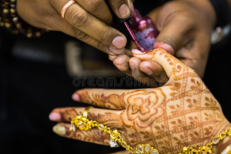 Manicurist doing manicure to indian bride hand lacquer polish, painting fingernails, royalty free stock image