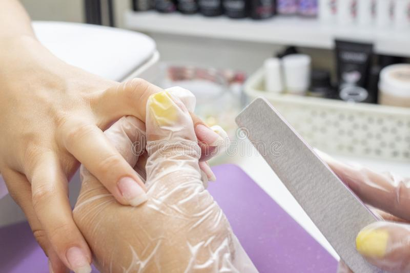 A manicurist makes a manicure for a girl, files her nails with nail file for royalty free stock image