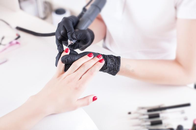 Manicurist, nail artist handles nails with manicure milling cutter. Beauty service, nail salon, health care and cosmetics. Close up stock photos