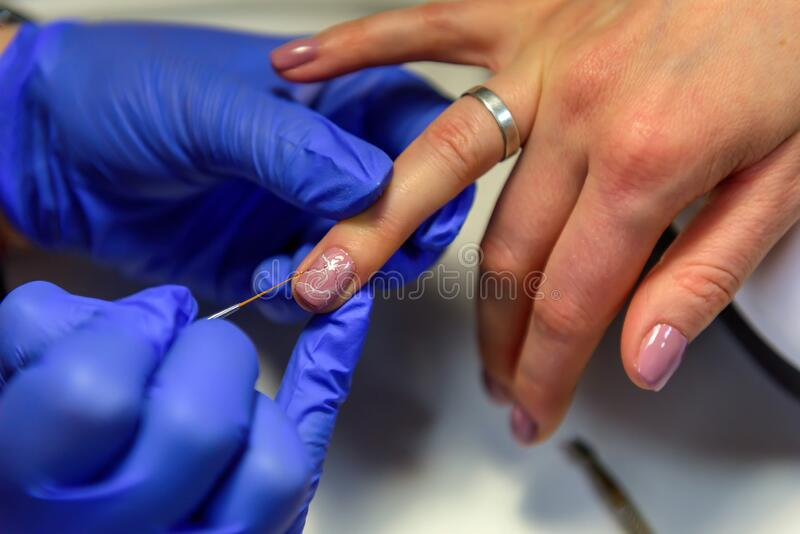Manicurist painting nails to female client, close-up. Beautician doing art design on nails. Professional hand and nail care in royalty free stock photos