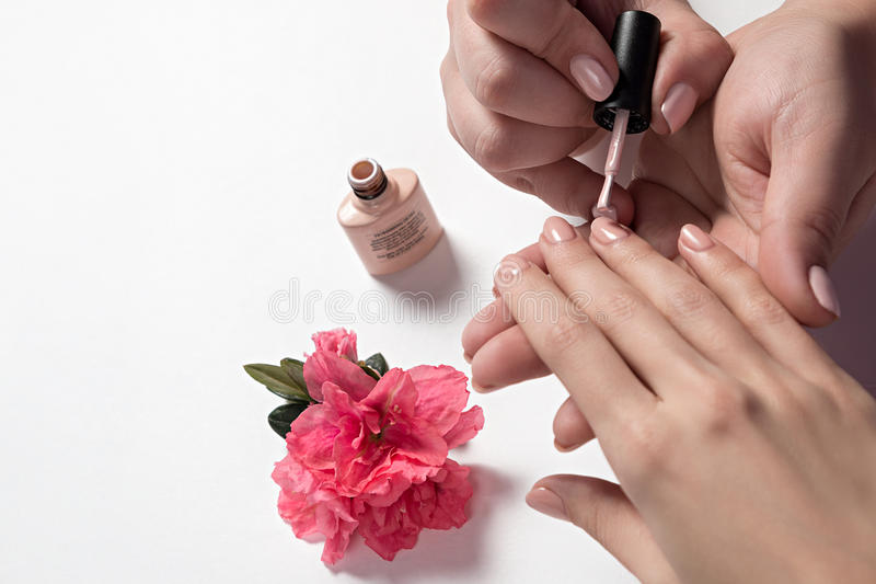 Manicurist paints nails to a customer. Closeup shot of a woman in a nail salon receiving a manicure by a beautician with nail file. Woman getting nail manicure royalty free stock image