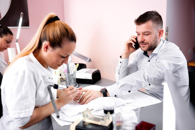 Manicurist rounding the shape of nail with electric nail machine royalty free stock photos