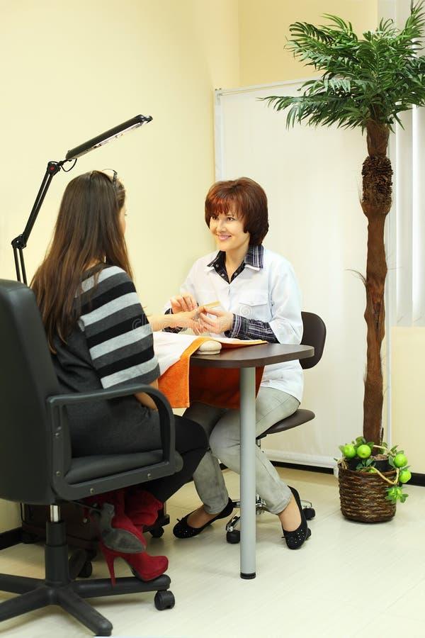 Manicuristen gör manicuren för kvinna royaltyfria bilder