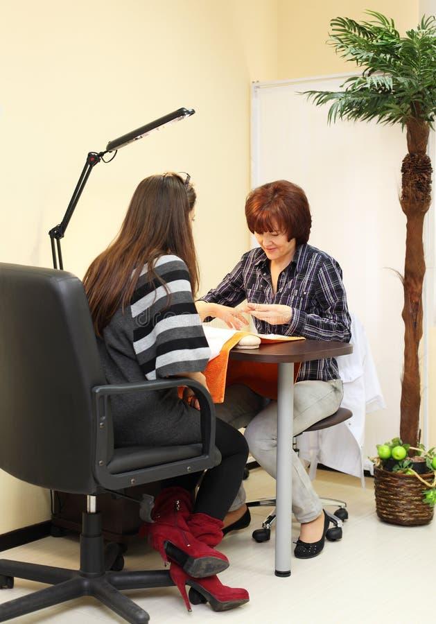 Manicuristen gör manicuren för kvinna arkivbild