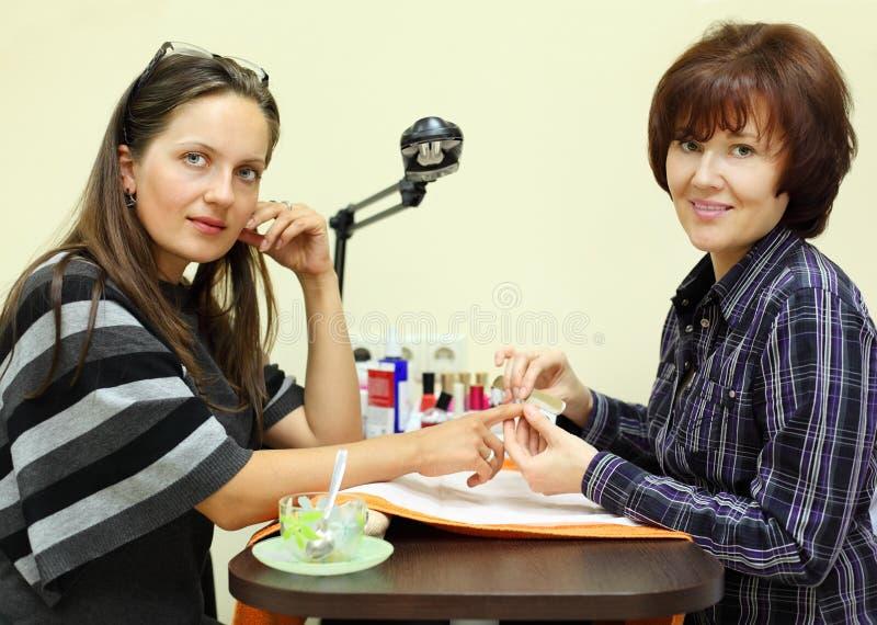 Manicuristen gör manicuren vid nailfile för kvinna royaltyfri foto