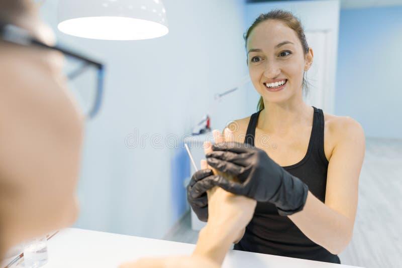 Manicuro de sorriso novo da menina que faz o tratamento de mãos profissional Cuidado do prego e da mão no salão de beleza fotos de stock royalty free