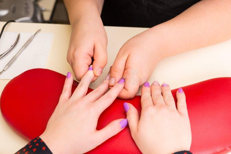 Manicuro Massaging Fingers do cliente no tratamento de mãos imagens de stock royalty free