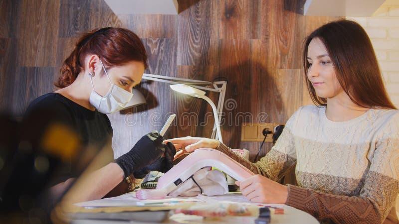 Manicuro na máscara médica que faz o tratamento de mãos para a mulher atrativa no salão de beleza fotos de stock
