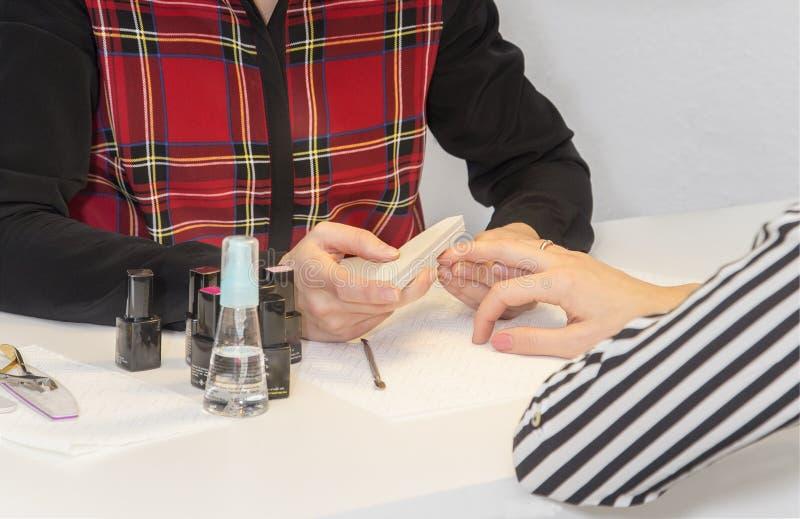 Manicuro que faz o tratamento de mãos no salão de beleza imagem de stock