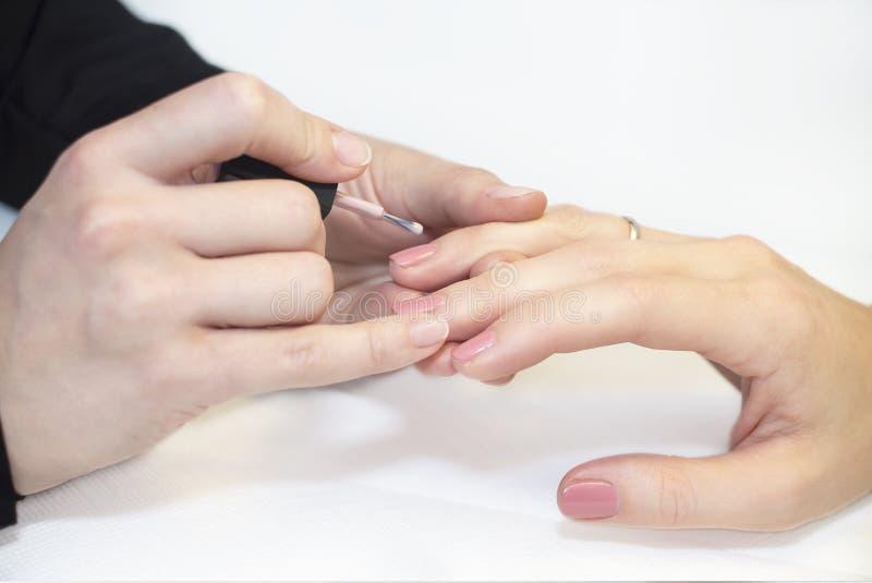 Manicuro que faz o tratamento de mãos no salão de beleza foto de stock