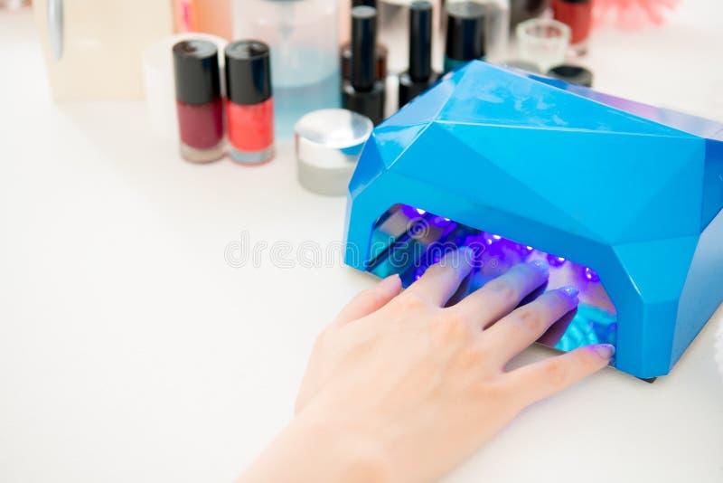 Manicuro que usa el secador portátil de la luz UV imagenes de archivo
