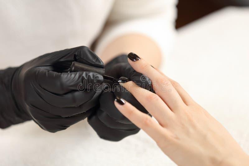 Manicurzysta maluje klientów gwoździe w czerni zdjęcia stock