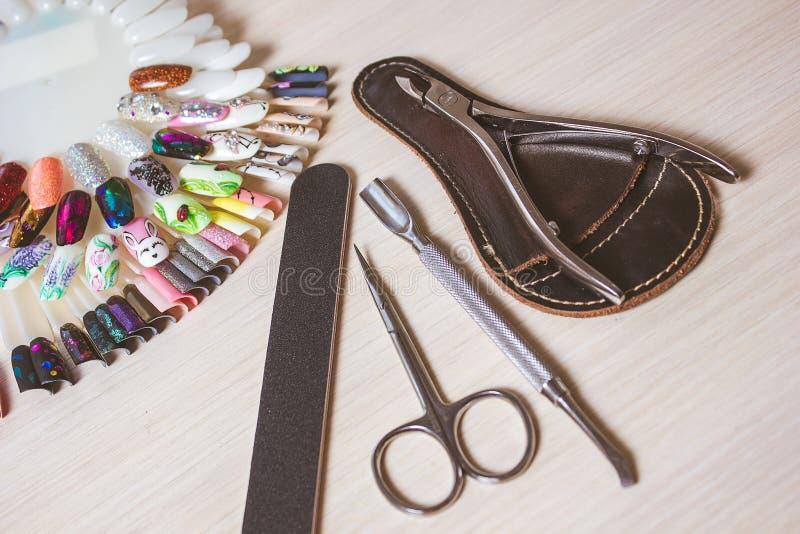 Manicurzysta praca z manicure'u setem i gwoździa połysk dla ręk dbamy białego tła odgórnego widok fotografia stock