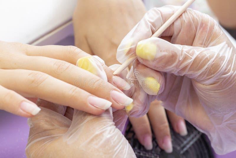 Manicurzysta robi manicure'owi dla dziewczyny traktowanie oskórek z kijem zdjęcia royalty free