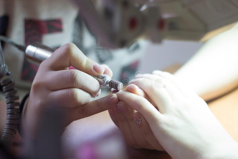Manicurzysta robi manicure procedurze z maszyną na manicurze t obrazy royalty free