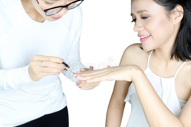 Manicurzysta stosuje gwoździa połysk jej klient obraz royalty free