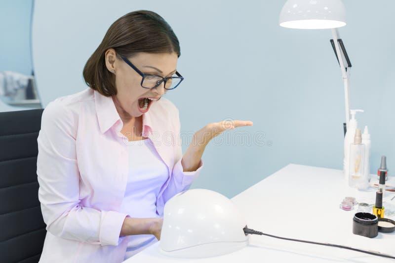 Manicurzysta używa pozafioletową lampę dla załatwiać gel gwoździa połysk Przybija opiekę w piękno salonie i wręcza, kobieta wrzas obrazy royalty free