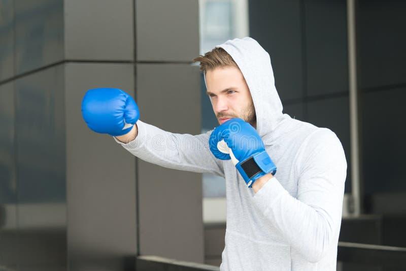 Manidrottsman nen på koncentrerad framsida med sporthandskar som öva boxas stansmaskin, stads- bakgrund Utbildning av hans boxnin arkivfoton