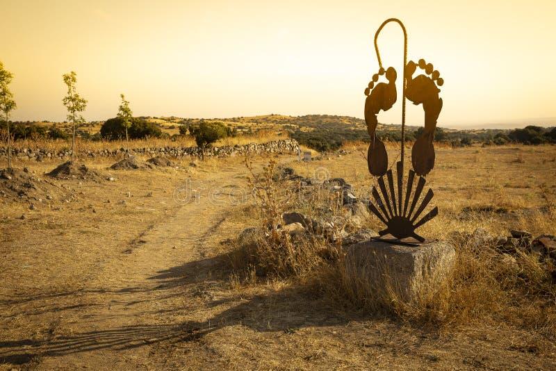 Manier aan Santiago - roestige metaalstructuur met een wandelstok, voeten en shell stock foto
