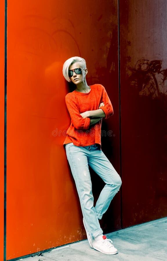Manier blond meisje die zich dichtbij rode muur op stadsstraat bevinden royalty-vrije stock afbeeldingen