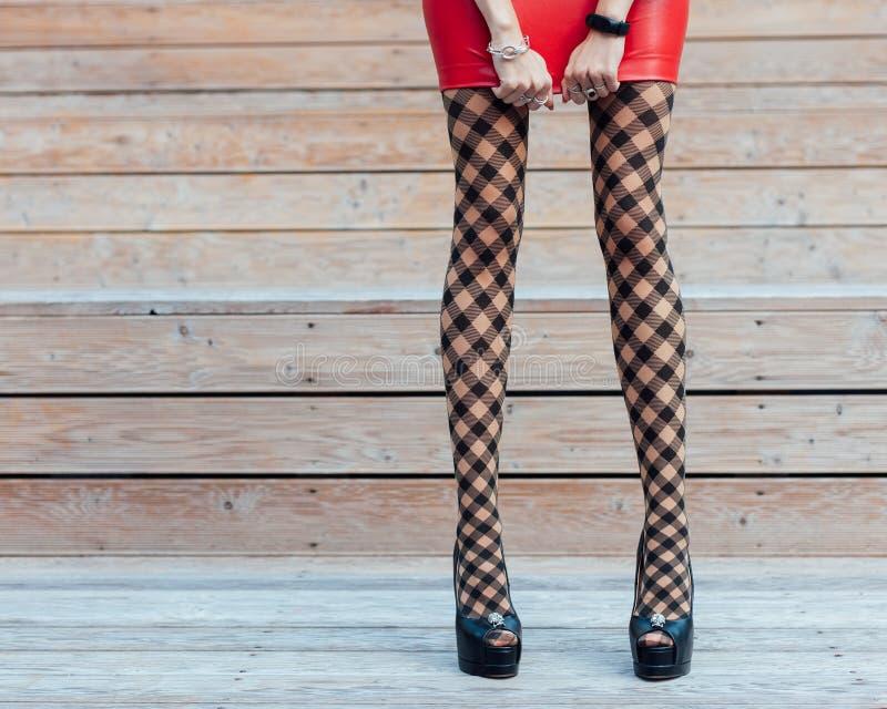 Manier Een zeer sexy meisje met lange benen in modieuze, visnetkousen, een korte rode leerrok en zwarte high-heeled schoenen stock afbeelding